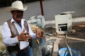 """Don Lupe demonstrates how """"confib"""" bricks are made. The bricks are about the same size as a cinder-block. For one step in the production process, washing machines are used in mixing pulp. (Photo by Kyle Wasson)"""